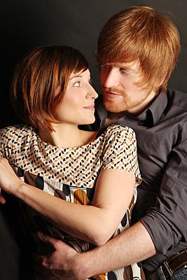 Portrait eines jungen Paares, auf dem der Mann seinen Arm von hinten um die Taille der Frau legt und sich beide anschauen.
