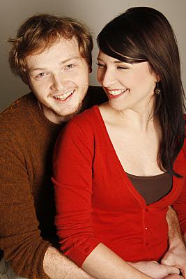 Portraitaufnahme eines jungen Paares von schräg oben, bei dem die Frau auf dem Schoß des Mannes sitzt, lächelnd zur Seite schaut, während der Mann in die Kamera lächelt.