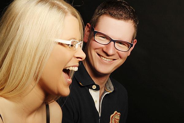 Teilweise seitliches Portrait eines Paares vor schwarzem Hintergrund, bei dem die blonde Frau im Vordergrund seitlich zu sehen ist, während der Mann von weiter hinten in die Kamera lächelt.