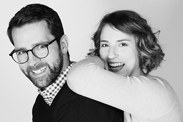 Schwarz-weißes Portraitfoto eines Paares, bei dem die Frau mit angewinkelten Armen auf dem Rücken des Mannes lehnt und beide in die Kamera blicken.