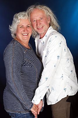 Portraitfoto eines Paares vor blauem Hintergrund, auf dem beide lachend in die Kamera schauen.