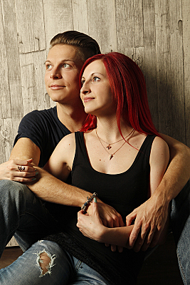 Junges Paar im Portrait aufgenommen, das verträumt an der Kamera vorbei in diesselbe Richtung schaut.