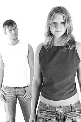 Schwarz-weißes High-Key Portrait eines jungen Paares, das stehend mit etwas Abstand zueinander entspannt in Richtung Kamera blickt.