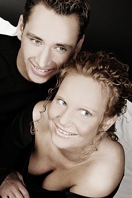 Portrait eines Paares das lächelnd nach oben an der Kamera vorbei blickt.