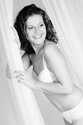Erotikfoto junge, lächelnde Frau in weißer Reizwäsche, die einen hängenden Tüllvorhang festhält.