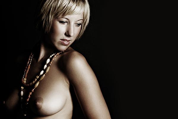 Erotikfoto junge Frau mit nacktem Oberkörper und zwei Holzketten um den Hals, die mit leicht geöffnetem Mund über ihre Schulter schaut.