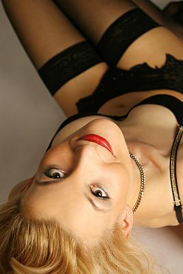 Erotikfoto blonde Frau mit roten Lippen und schwarzer Reizwäsche mit Strapsen von oben.