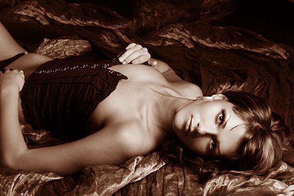 Erotikfoto auf dem Rücken liegende Frau mit schwarzer, leicht geöffneter Kossage, die eine Hand an die Brust hält und lasziv in die Kamera blickt.