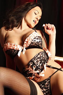 Erotikfoto auf dem Rücken liegende Frau mit schwarz-rosa Reizwäsche und lasziv geöffnetem Mund.
