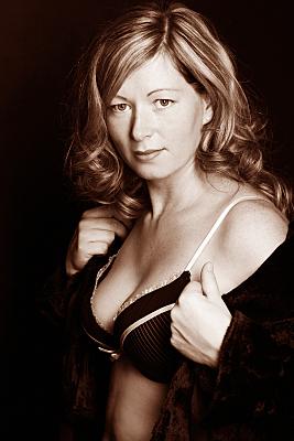 Erotikfoto Frau mit gelocktem, blonden Haar und rosa-schwarzem Rüschen-BH, die sich einen Mantel abstreift.