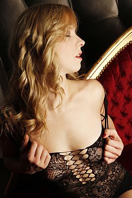 Erotikfoto Frau mit langen, blonden Haaren sitzt auf einem roten Samtsofa und schaut sich lasziv mit geöffnetem Mund über die nackte Schulter.