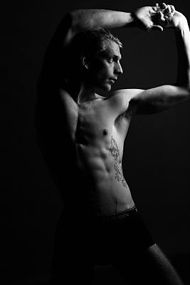 Low-Key Erotikfoto eines oberkörperfreien Mannes, der über seine linke Schulter und den ausgestreckten Arm in die Ferne blickt.