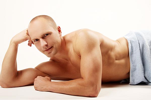 Erotikfoto eines Mannes, oberkörperfrei, auf dem Bauch liegend und mit dem rechten Arm den Kopf stützend.