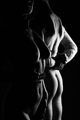 Schwarz-weißes Erotikfoto Paar, bei dem im Hintergrund die Rückansicht eines nackten Mannes und im Vordergrund die Frontansicht einer nackten Frau zu sehen ist.