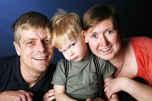 Familienfoto Eltern und Kind, die ihr Kind zwischen sich haben, das skeptisch in die Kamera blickt.