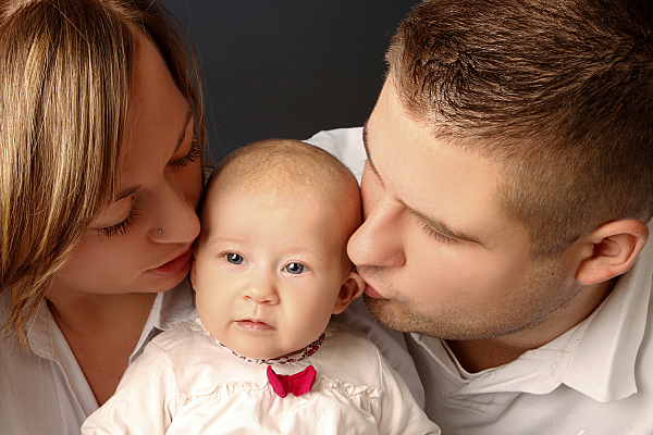 Familienfoto Eltern, die beide die Stirn ihres zwischen sich sitzenden Kindes küssen.