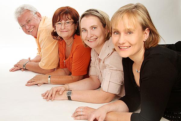 Familienfoto drei Frauen unterschiedlichen Alters und ein Mann, alle auf dem Bauch in schräger Linie liegend.