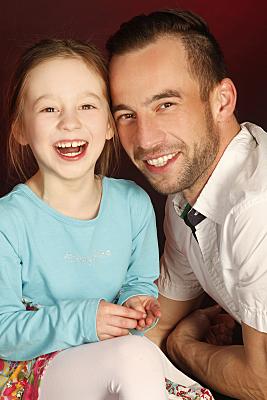 Familienfoto lächelnder Vater mit lachender Tochter neben sich.