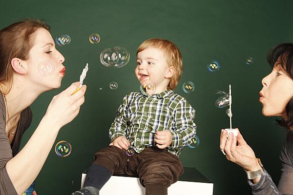 Familienfoto zweier Frauen, die für ein zwischen sich sitzendes Kleinkind Seifenblasen pusten.