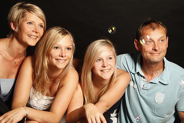 Familienfoto Vater, Mutter und zwei Töchter in der Mitte, die schwebenden Seifenblasen nachschauen.