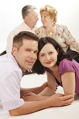 Familienfoto lächelndes, auf dem Bauch liegendes Pärchen im Vordergrund, sich liebevoll anschauende, sitzende Großeltern im Hintergrund.