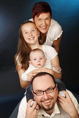 Familienfoto Vater, Mutter und zwei Kinder in weißen Oberteilen hintereinander stehend vor dunklem Hintergrund.