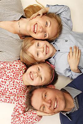Familienfoto Vater, Mutter und zwei Kinder auf einem hellen Untergrund auf dem Rücken liegend und nach oben schauend.