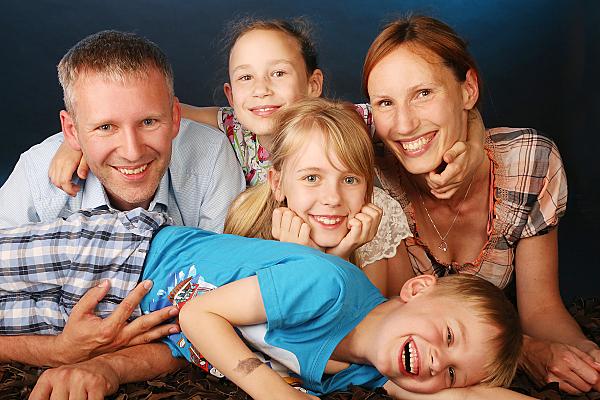 Familienfoto auf dem Bauch liegende Eltern mit drei Kindern.