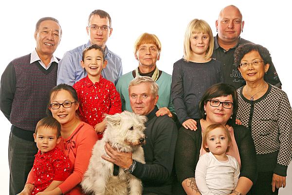 Familienfoto Großfamilie mit Hund vor hellem Hintergrund.