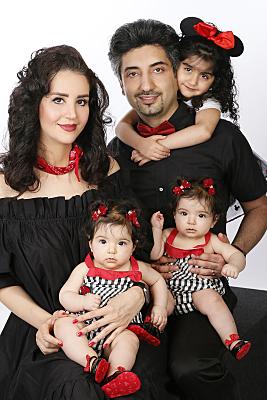 Familienfoto fünfköpfige Familie, alle in schwarz-roter Kleidung.