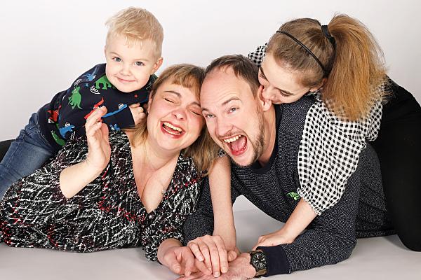 Familienfoto vierköpfige Familie, die lachend auf dem Bauch liegt und die Kinder auf den Rücken der Eltern liegen.