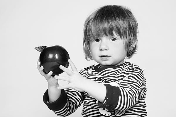 Low Key Kinderfoto Kleinkind in geringeltem Shirt, das einen Apfel in den ausgestreckten Armen nach oben hält.
