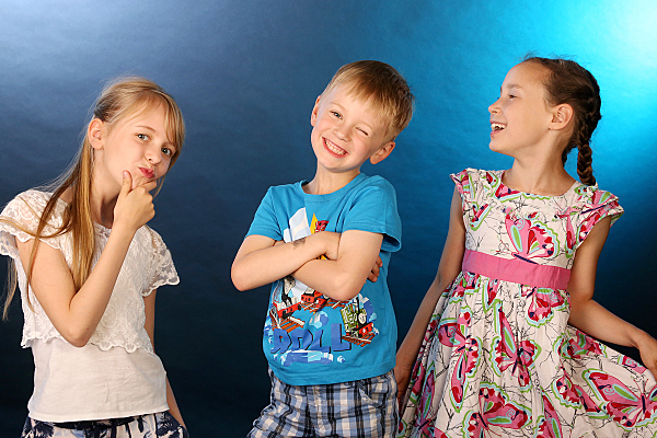 Kinderfoto von drei stehenden Kindern vor einem blauen Hintergrund, die alle fröhlich lachen.