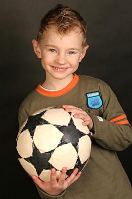 Kinderfoto Portrait lächelnder Junge in grünem Shirt, der einen Fußball vor seinem Oberkörper hält.