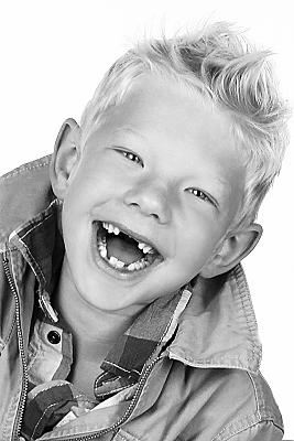 Low Key Kinderfoto lachender Junge mit Zahnlücke und kurzen, blonden Haaren.