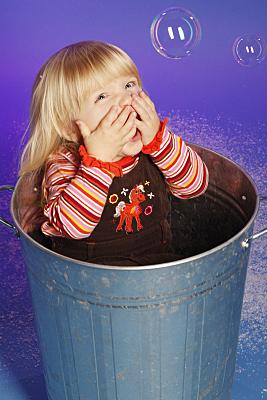Kinderfoto Mädchen in geringeltem Pulli mit langen, blonden Haaren vor lila Hintergrund, das sich den Mund mit beiden Händen zuhält.