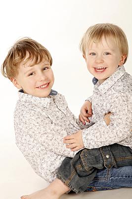 Kinderfoto zwei Kleinkinder in hellen Blusen, die sich gegenüber stehen und in die Kamera lächeln.
