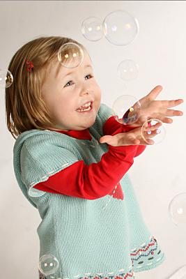 Kinderfoto Mädchen in grün-rotem Pulli, das staunend Seifenblasen anschaut und nach ihnen greift vor hellem Hintergrund.
