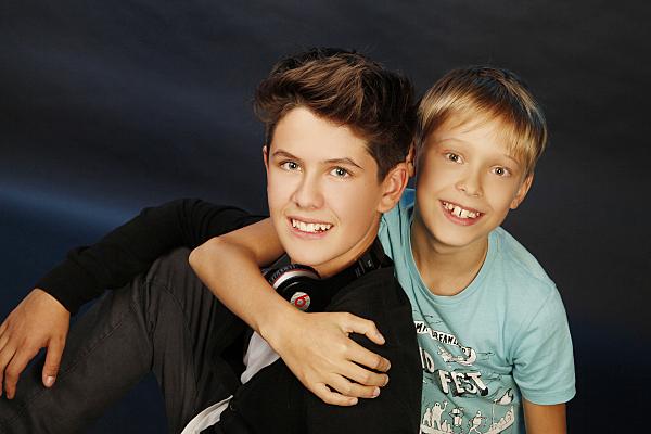 Kinderfoto zweier sitzender, sich aneinander lehnender Brüder vor dunklem Hintergrund.