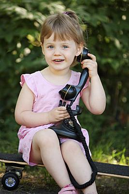 Kinderfoto lächelndes Mädchen mit schwarzem, alten Telefonhörer in der Hand vor einer Hecke.