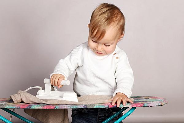 Kinderfoto Portrait Mädchen mit Zopf und weißem Pullover mit einem Bügeleisen in der Hand hinter einem Bügelbrett.