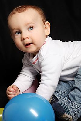 Kinderfoto sitzendes Baby in weißem Pulli und Jeans vor scharzem Hintergrund mit einem blauen Ball im Vordergrund.