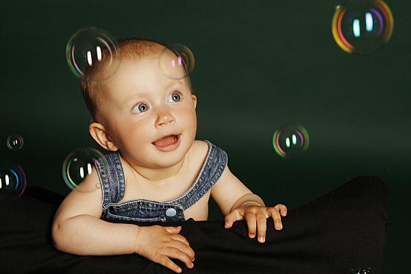 Kinderfoto Baby in Latzhose, das staunend Seifenblasen anschaut vor dunklem Hintergrund.