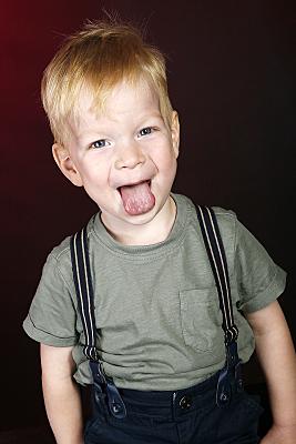 Kinderfoto Portrait blonder Junge, der die Zunge herausstreckt.