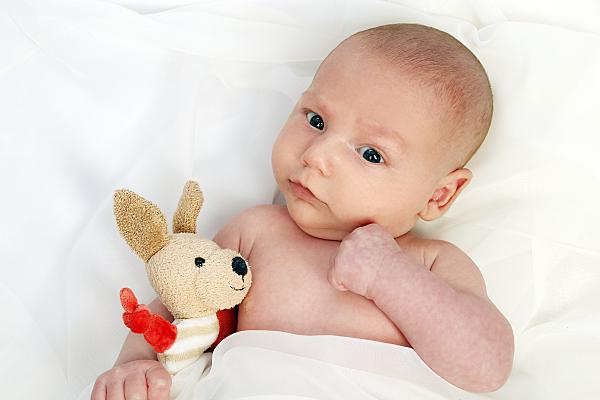 Ein Babyfoto mit einem kuschligen kleinen Stoffhase