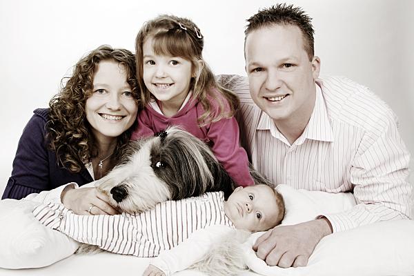 Tierfoto vierköpfige Familie mit Hund, die sich um ein Baby reiht.