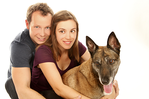 Tierfoto junger Mann, der seine Freundin vor sich umarmt, die einen Hund vor sich sitzen hat und diesen ebenfalls marmt.