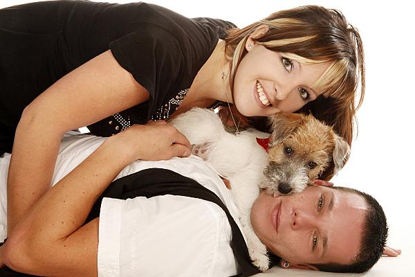 Tierfoto auf dem Rücken liegender Mann, der seinen kleinen Hund und seine Freundin auf seinem Bauch liegen hat.