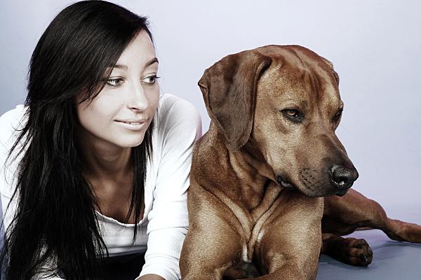 Tierfoto junge, auf dem Bauch liegende Frau, die neben ihrem Hund liegt vor hellem Hintergrund.