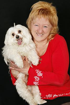 Tierfoto Frau in rotem Pulle, die ihren kleinen, hellen Hund vor sich hält vor dunklem Hintergrund.